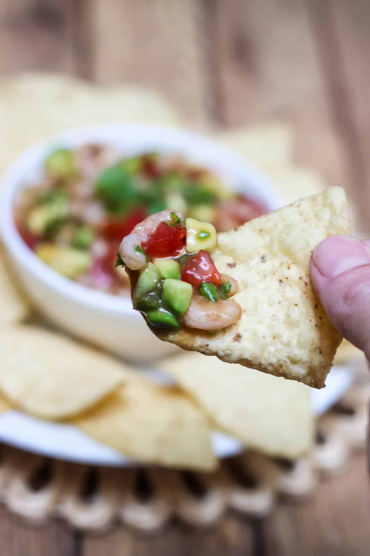 Shrimp Avocado Salsa close up on a tortilla chip with bowlful in background.