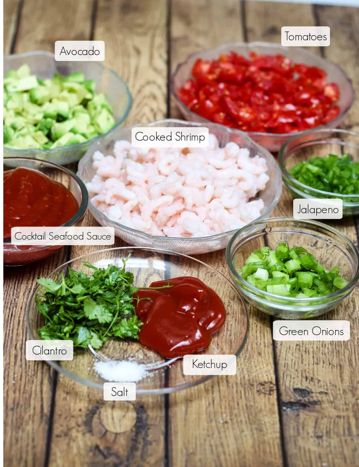 Ingredients in bowls for Shrimp Avocado Salsa with each labeled.