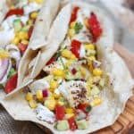 image of fish tacos with avocado, tomato and corn salsa in tortilla