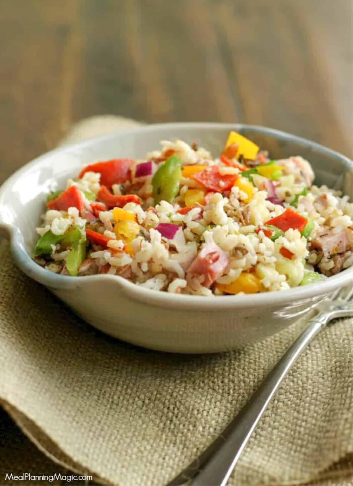 Italian Vegetable Wild Rice Salad in a pottery bowl on burlap napkin.
