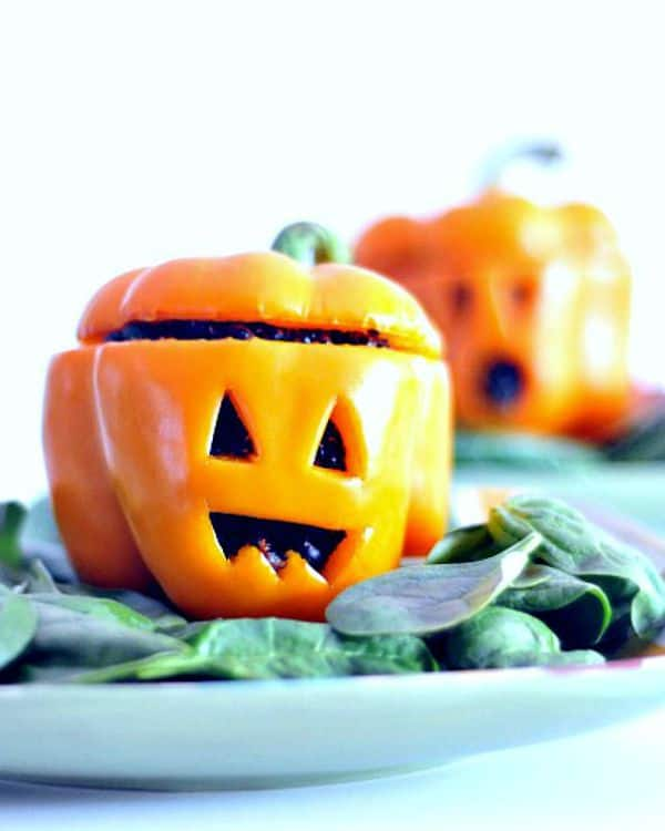 Orange bell pepper with Jack O Lantern face carved in it on a blue-green napkin