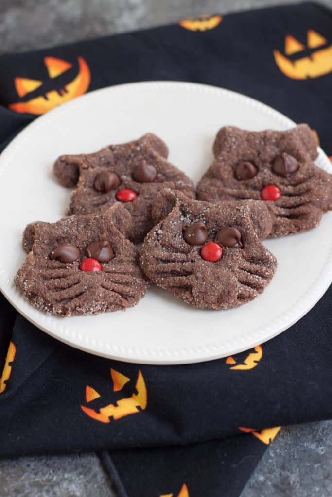 Chocolate cookies shaped and decorated like cat faces on a white plate with a black and jack-o-lantern face print napkin.