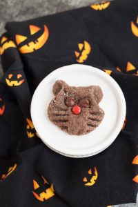 Single chocolate sugar cookie shaped and decorated like a cat face on a white plate with black and orange jack-o-lantern printed napkin.