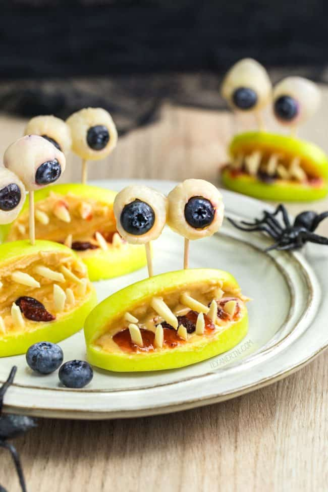 Image of apple slices with slivered almonds to look like teeth and white chocolate dipped blueberries for eyes on a white plate for a Halloween snack.