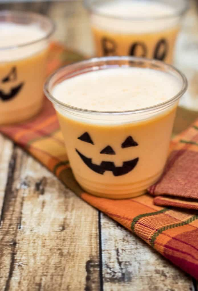 Orange Peach Smoothie in clear cups decorated for Halloween on orange plaid napkin.