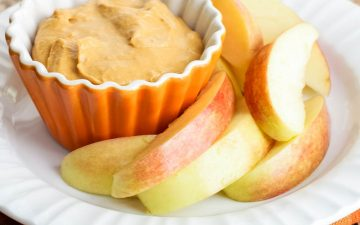 Pumpkin cream cheese dip in small orange cup with apple slices on a plate.