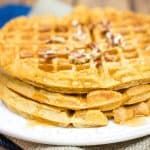 Stack of three pumpkin spice waffles with pecan and maple syrup topping on a white plate on blue napkin.