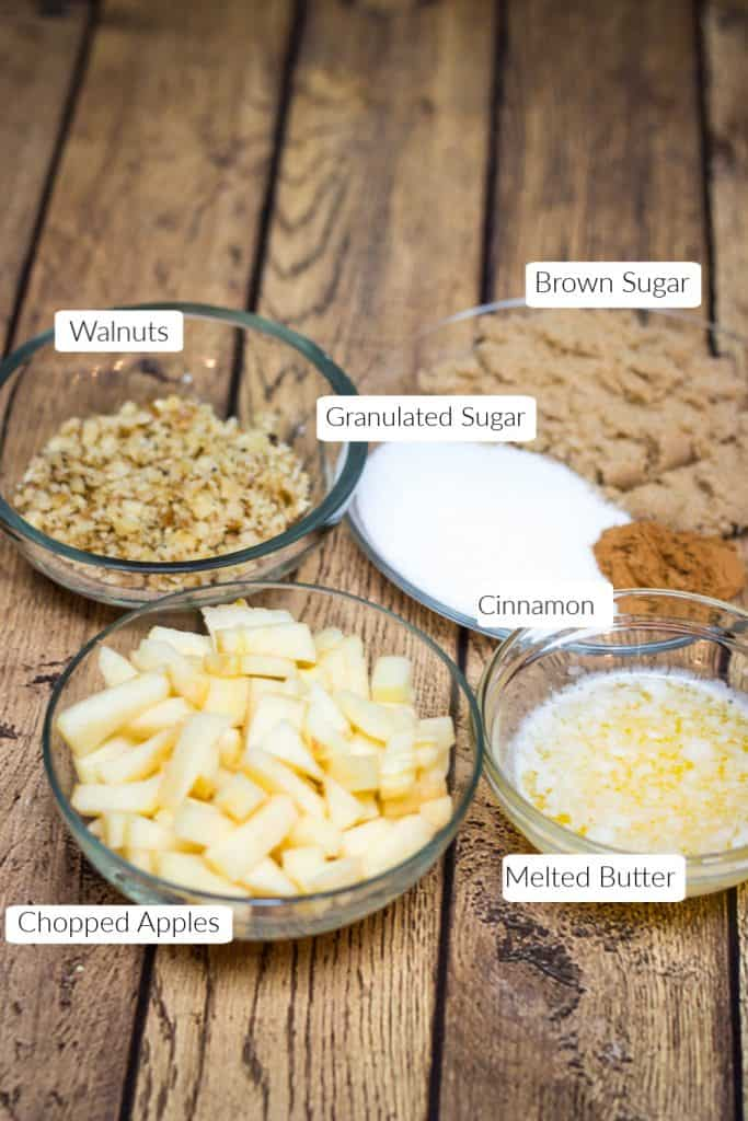 Labeled ingredients in bowls for apple cinnamon rolls filling.
