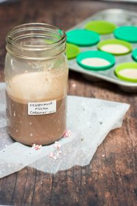 Peppermint Mocha Creamer in a mason jar with muffin tin and green silicone muffin cups of portioned out creamer for the freezer.