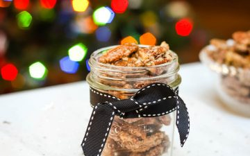 jar with black ribbon containing kahlua sugar pecans and colored lights of Christmas tree in background