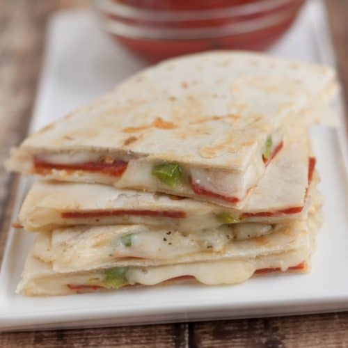 Stack of three pepperoni pizza quesadilla triangular slices on a white plate with small bowl of pizza sauce for dipping.