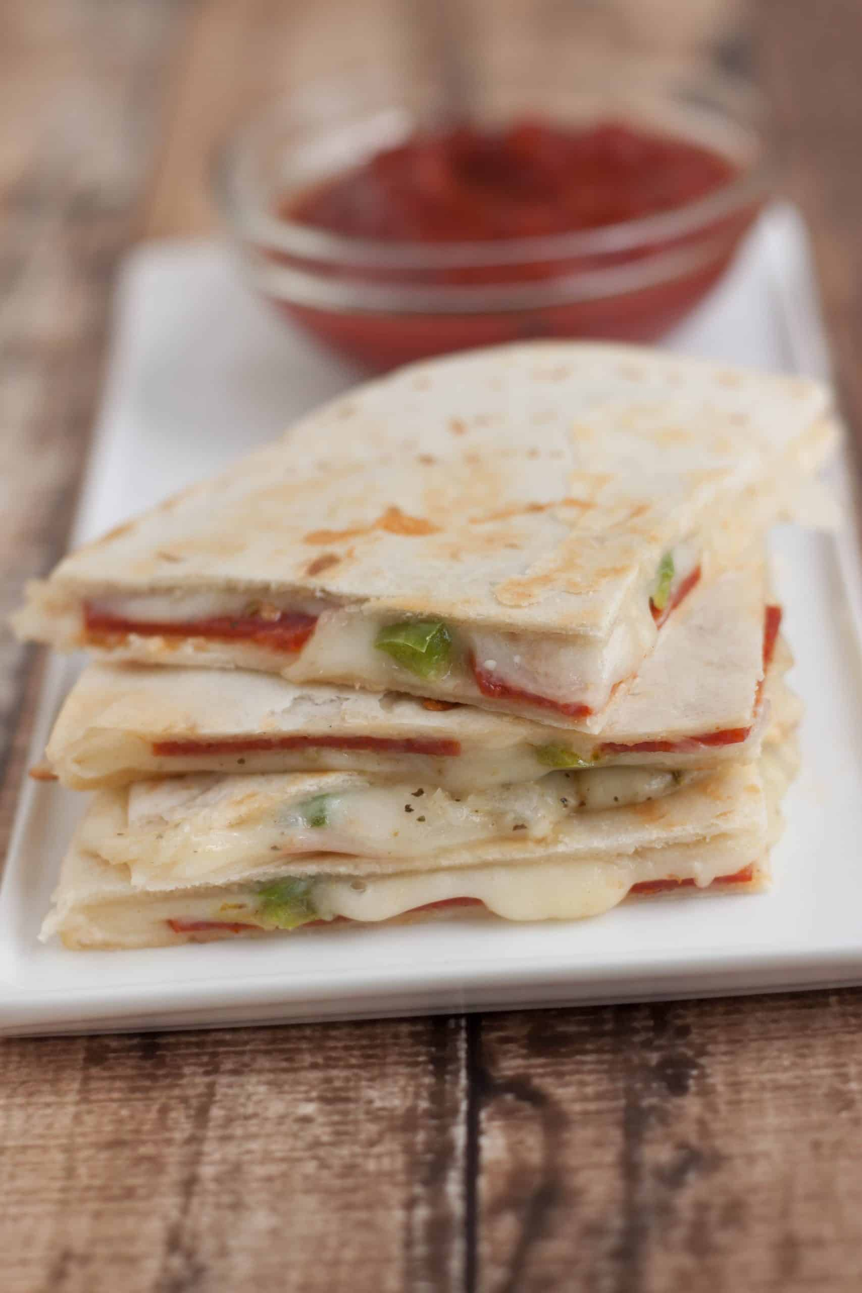 Image of pepperoni pizza quesadilla triangle slices on a white plate with small bowl of pizza sauce for dipping.