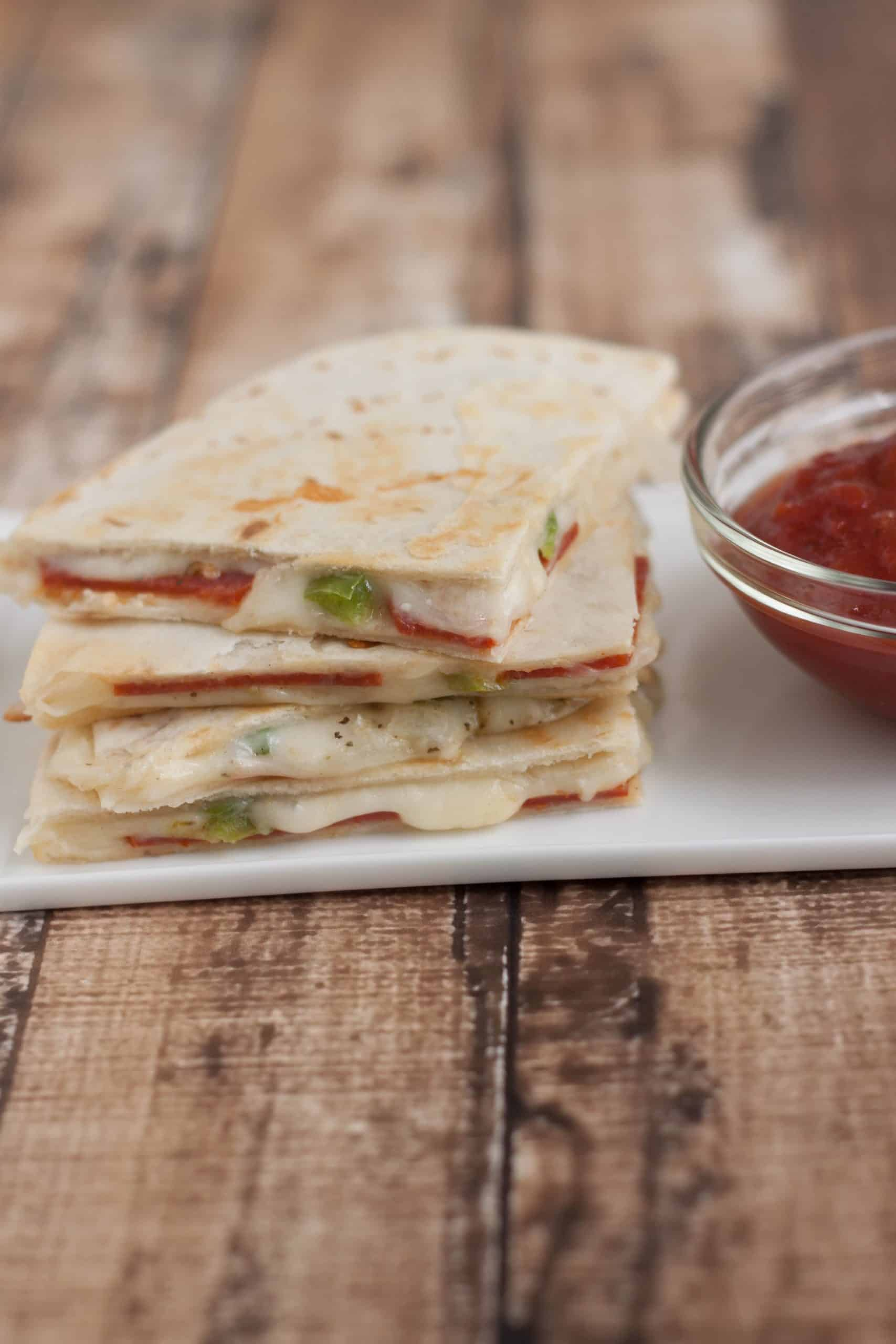 Stack of three pepperoni pizza quesadilla slices on a white plate with pizza dipping sauce on right side.