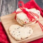 Heart shaped cherry and chocolate chip cookie cutter cookies with three in a stack wrapped in red ribbon on a small wooden cutting board on a red napkin.