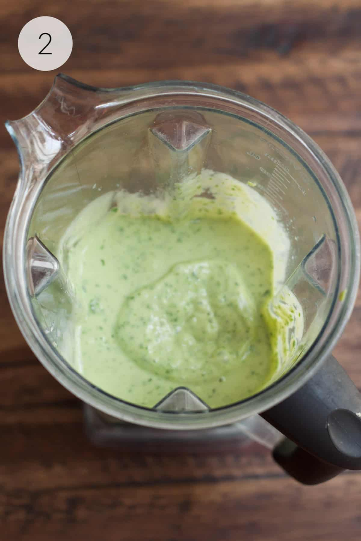 Blender jar with blended banana spinach and avocado smoothie.