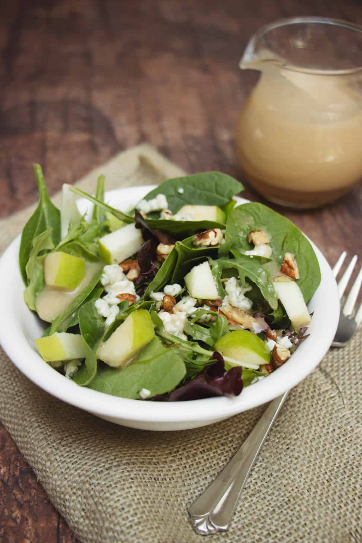 Salad with green apples, blue cheese and pecans in a white bowl on a burlap napkin with dressing in corner.