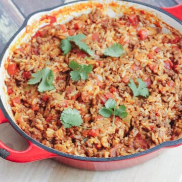 Red cast iron skillet with Spanish Rice with Ground Beef dish topped with cilantro leaves.