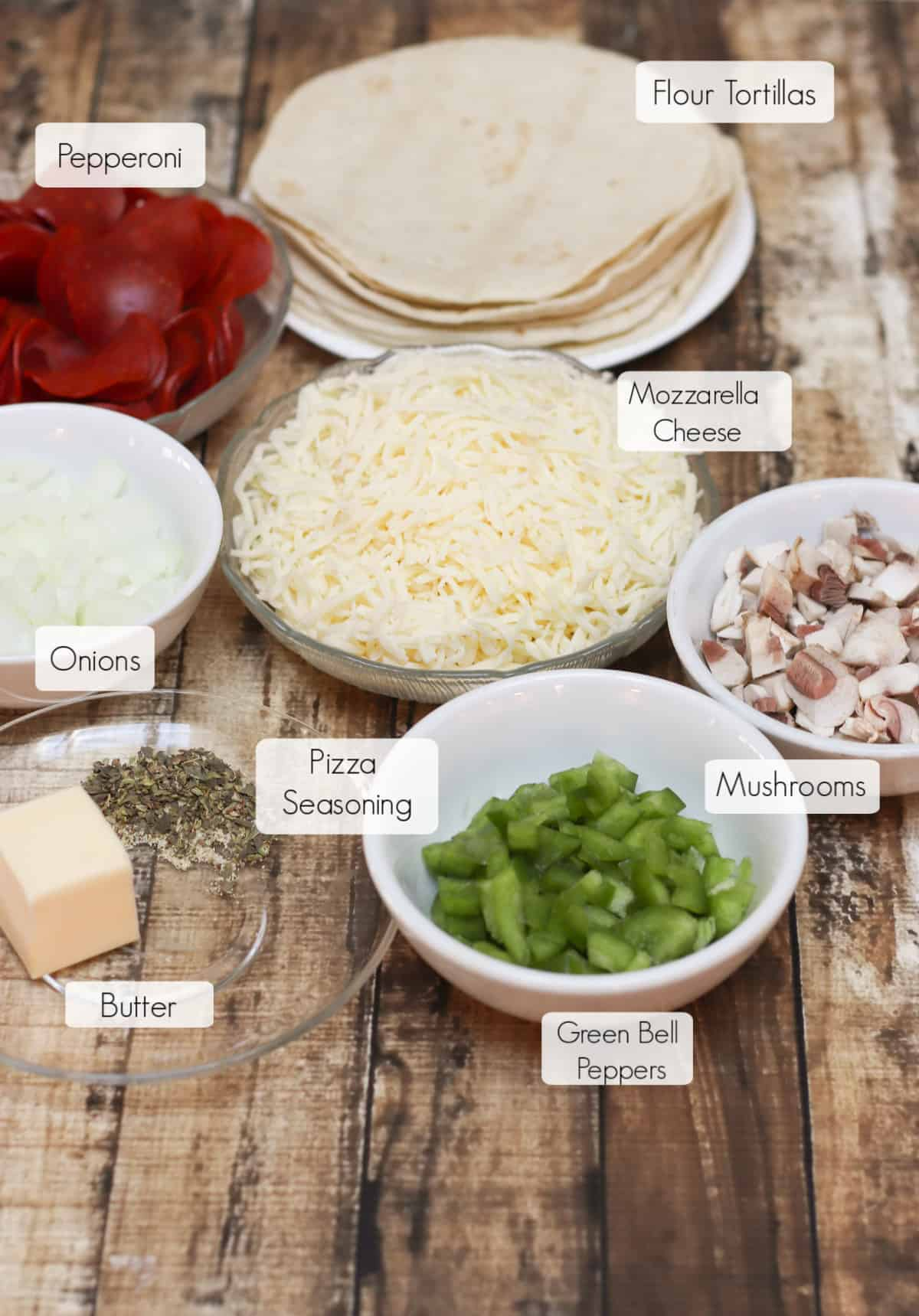 Ingredients in bowls with labels for making Pepperoni Pizza Quesadillas.