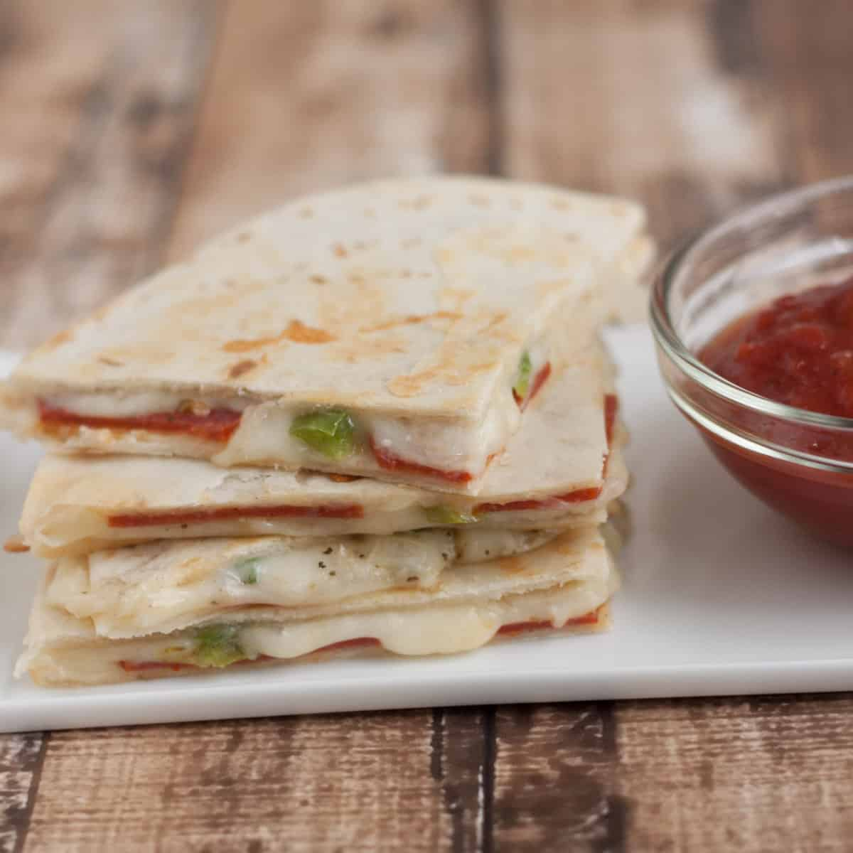 Stack of three Pepperoni Pizza Quesadilla slices with tomato dipping sauce in bowl on a white plate.