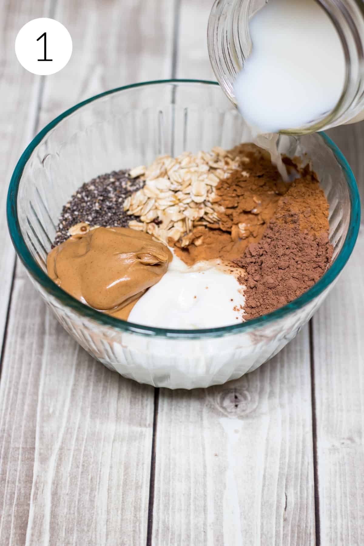 Glass bowl with oats, cocoa, chia seeds, cinnamon and peanut butter with milk being poured in.