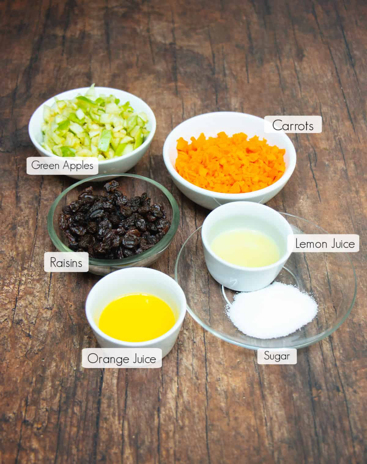 Ingredients in labeled bowls to make Apple Carrot Salad.