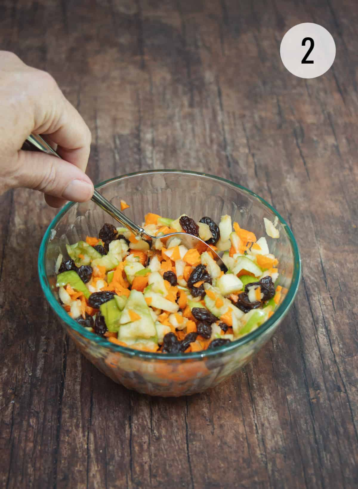 Stirring ingredients for Apple Carrot Salad with Raisins in a small bowl.