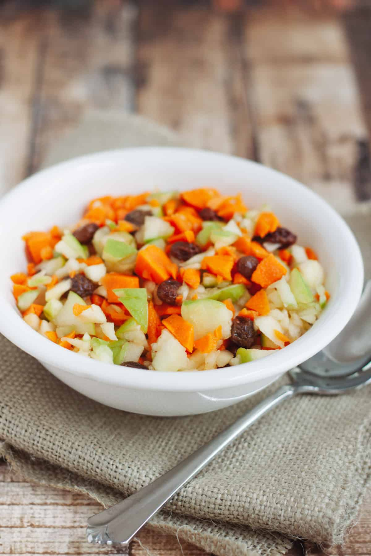 White bowl with finely chopped apples, carrots, and raisins on a burlap napkin with silver spoon.