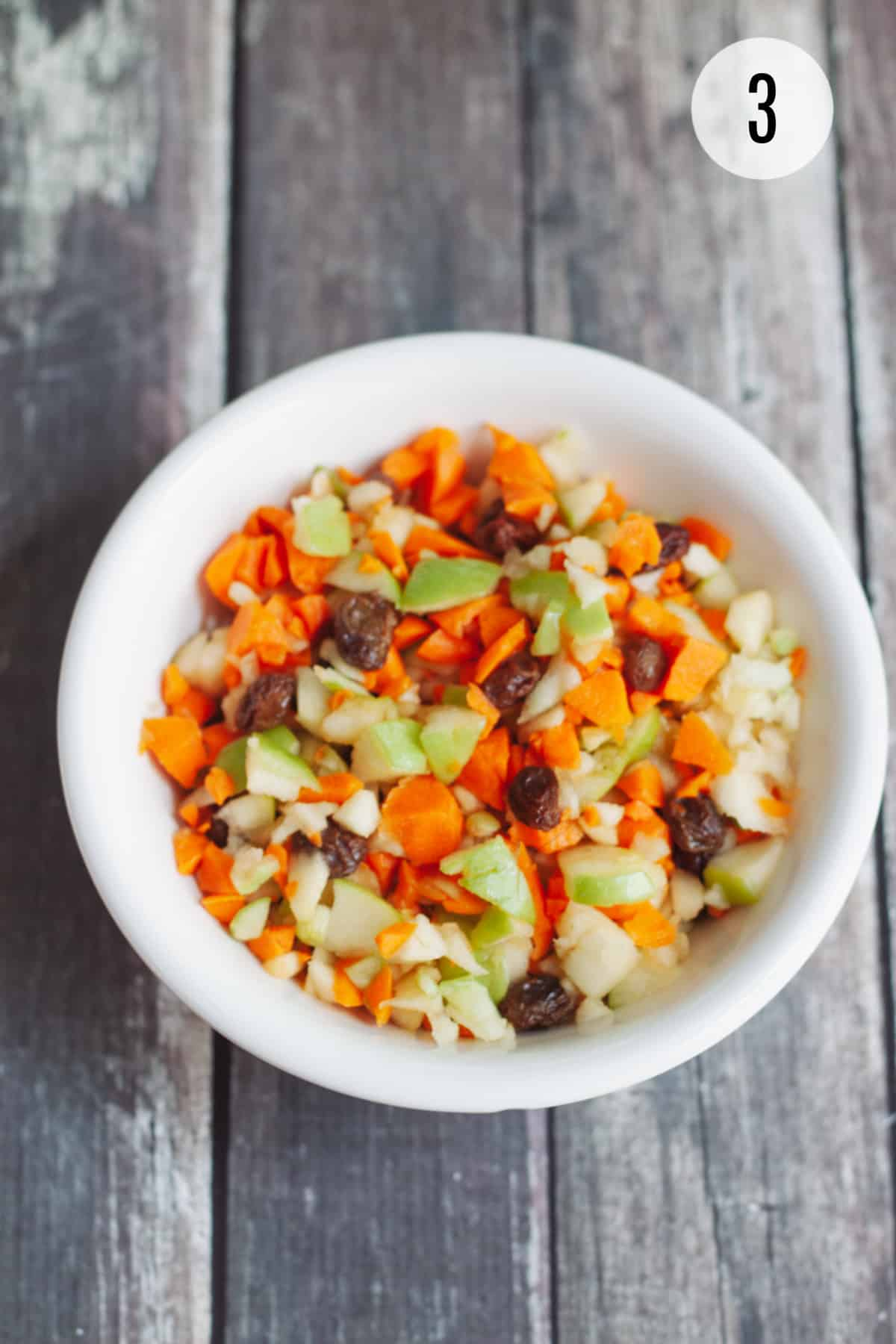 White bowl with Apple Carrot Salad with Raisins on a dark background.