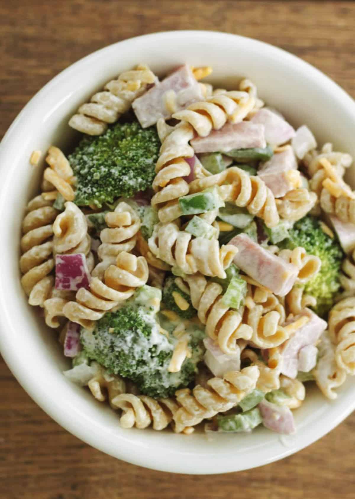 White bowl with pasta salad including broccoli, ham, fusilli pasta, purple onion, cheddar cheese.