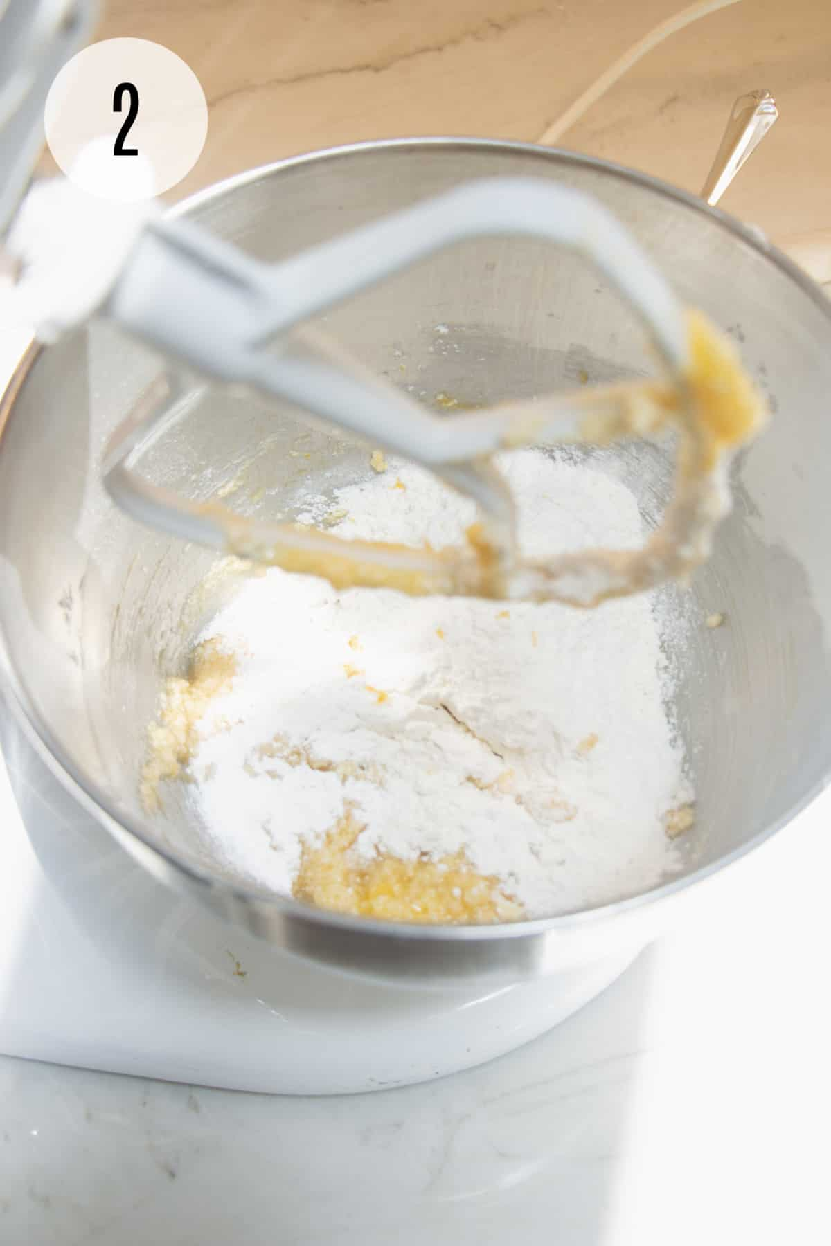 Butter sugar mixture with flour mixture for lemon cookies in a silver bowl mixed by a white mixer paddle.