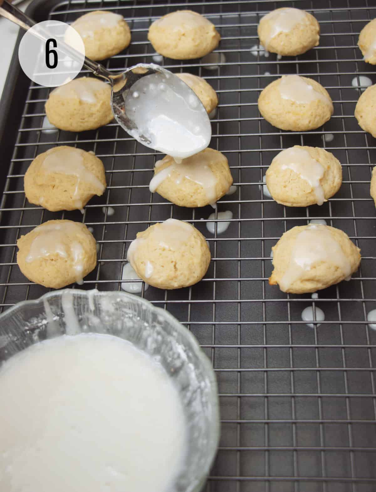 Silver spoon drizzling white glaze onto yellow cookies on a cooling rack on a baking tray with bowl of glaze in lower left.