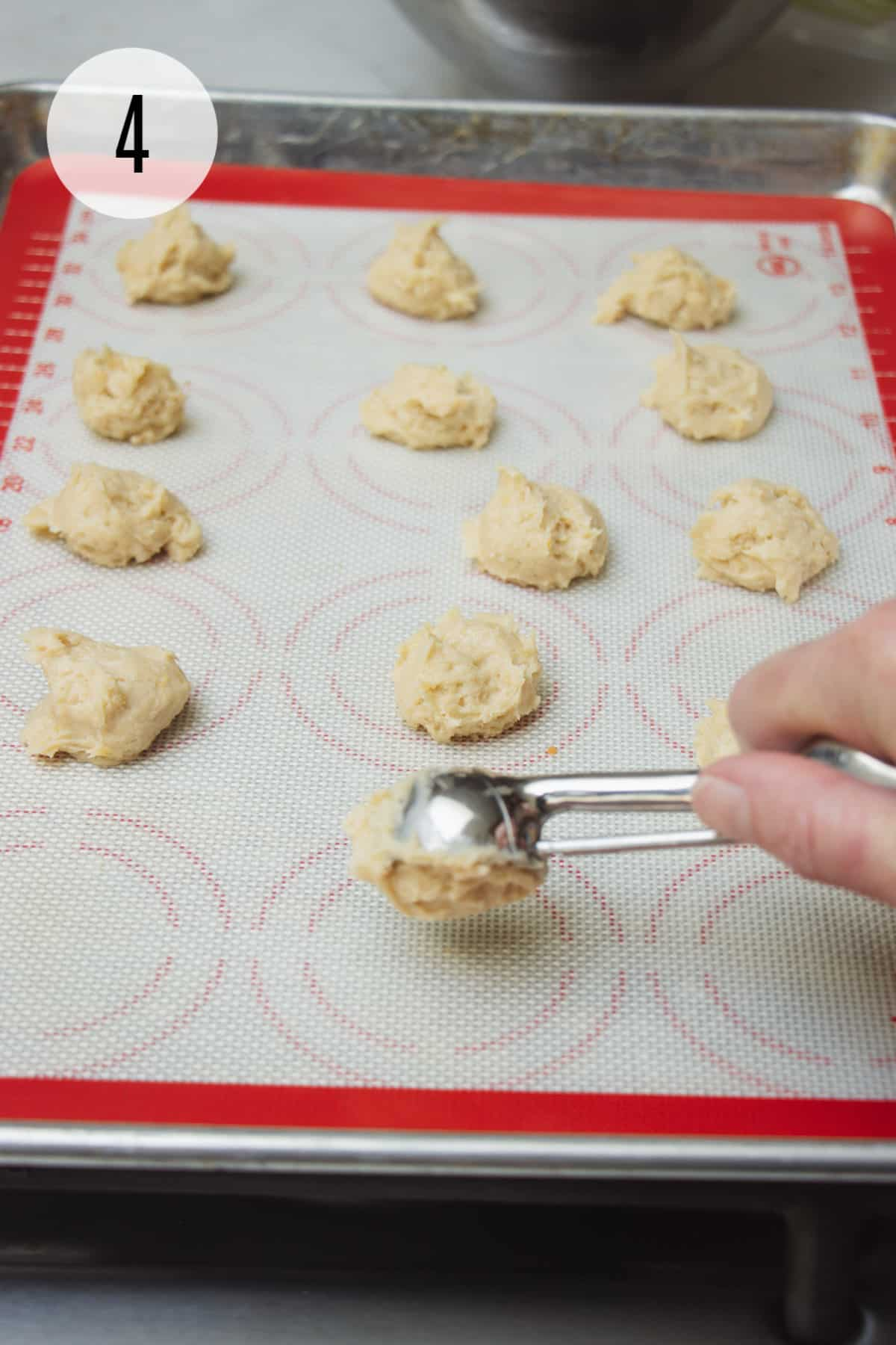 Scoop dropping cookie dough on to a red and white silicone baking mat with cookie dough balls on tray.
