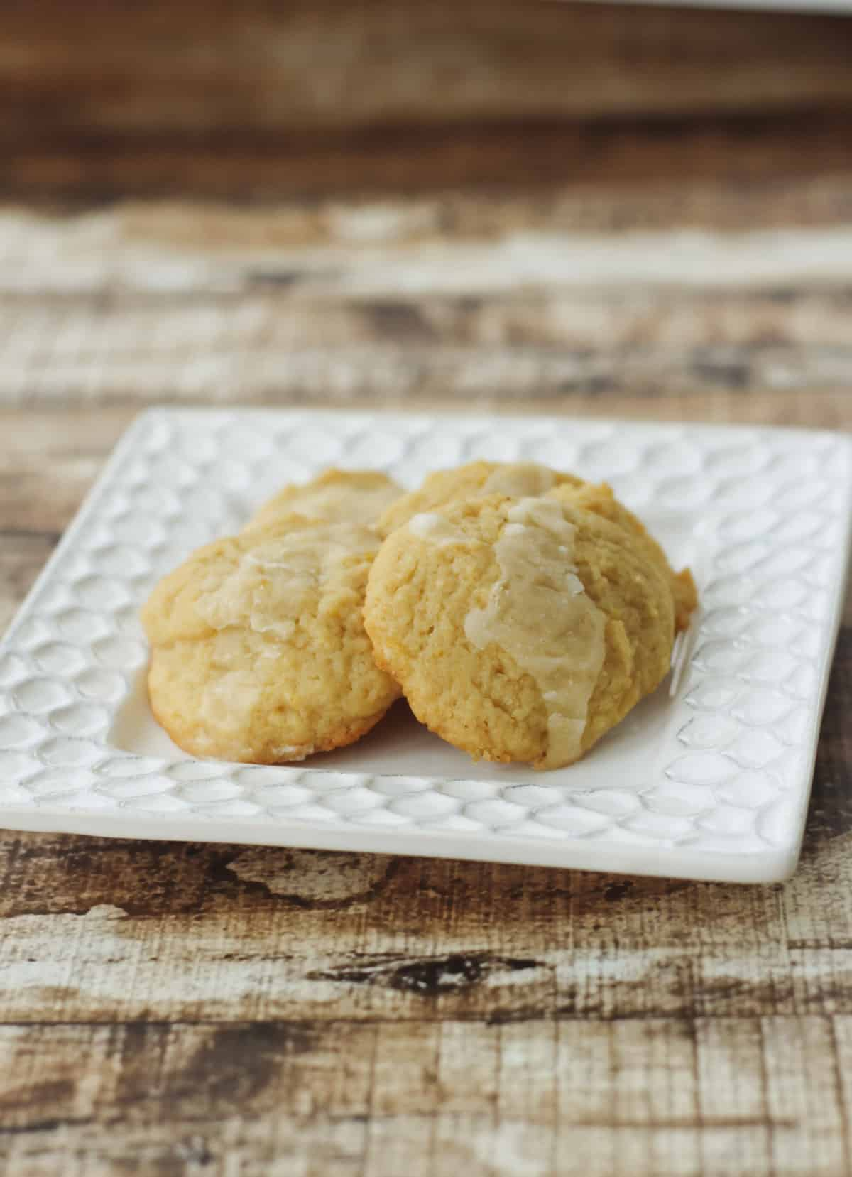 Small pile of lemon cookies with glaze on a square white plate on a wooden background.
