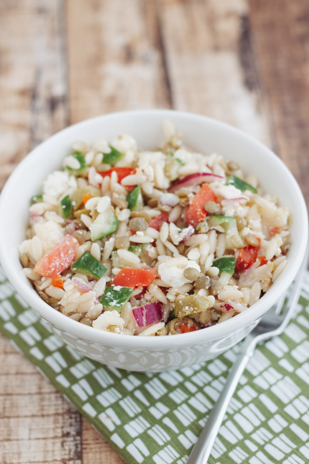 White bowl of Greek Orzo Salad with Lentils and fresh tomatoe and cucumbers in a white bowl on a green and white napkin.