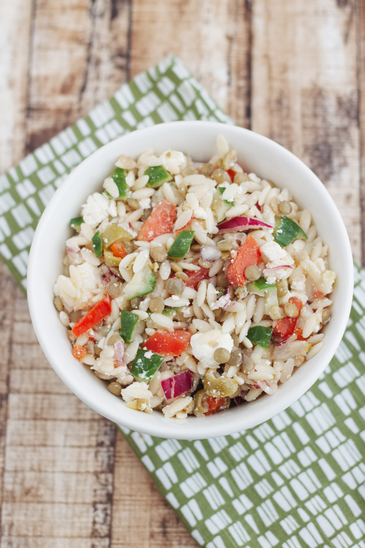 Top view image of Greek Orzo Salad with Lentils in a white bowl on a green and white napkin.