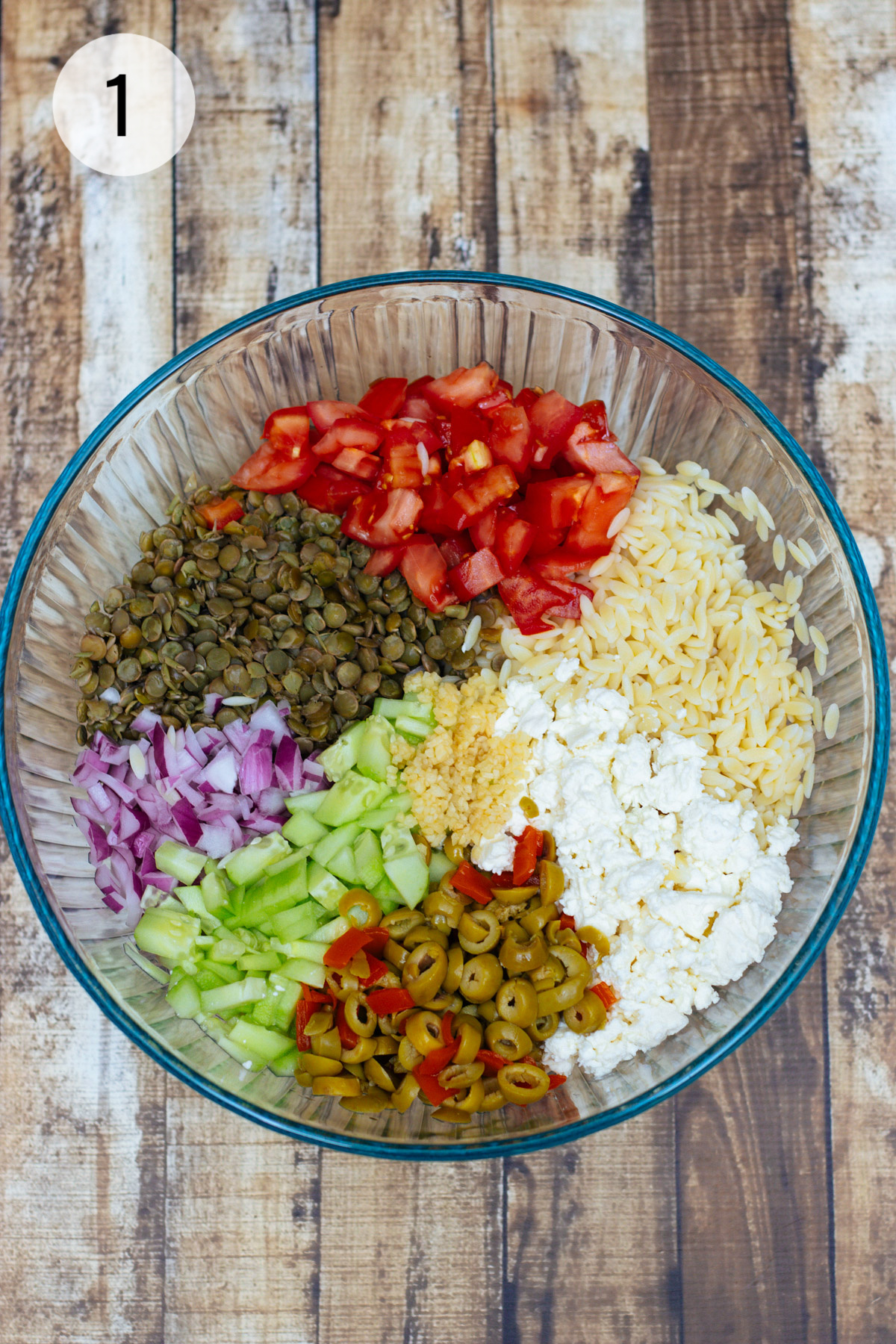 Clear bowl with ingredients for Greek Orzo Salad with Lentils, olives, tomatoes, cucumbers, feta and purple onion.