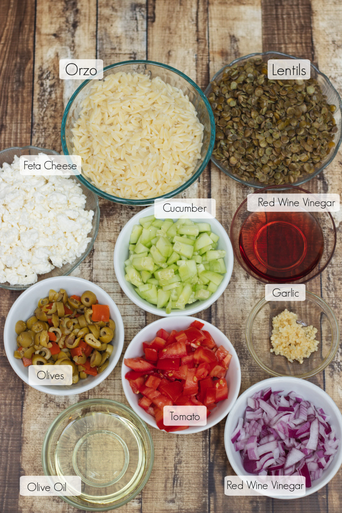 Image of ingredients in bowls with labels for Greek Orzo Salad with Lentils.