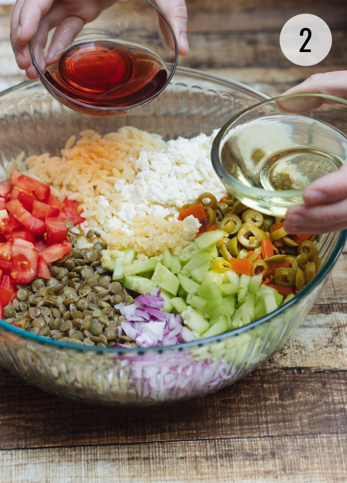 Ingredients for a Greek Orzo Salad with Lentils in a clear bowl with olive oil and red wine vinegar about to be poured in.