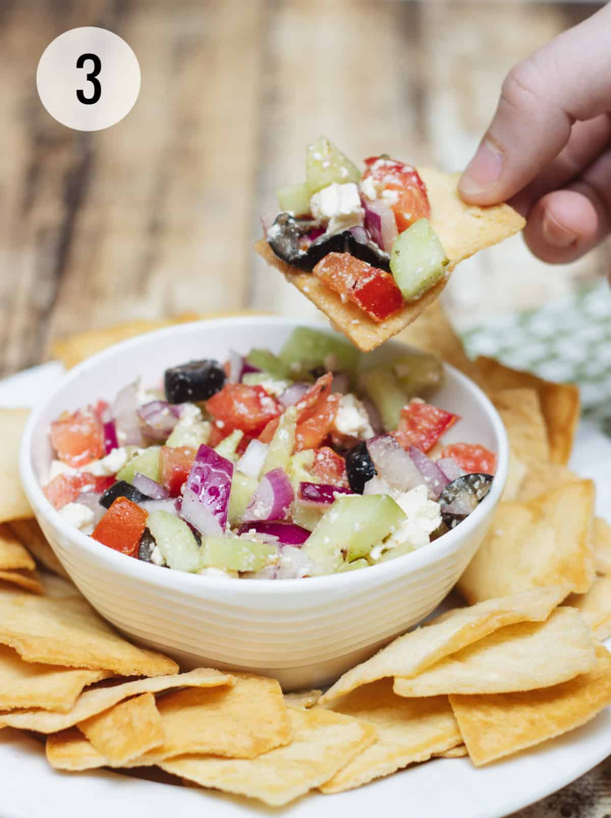 Greek salsa with tomatoes, cucumbers, black olives and feta cheese on a pita chip with white bowl of salsa and chips.