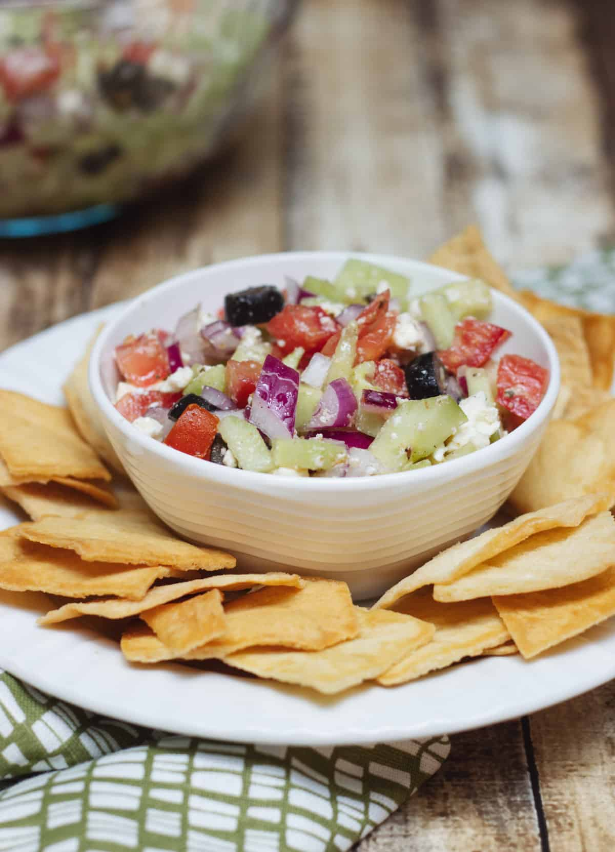 Greek salsa with tomatoes, purple onion, black olives, cucumber and feta cheese in a white bowl surrounded by pita chips.