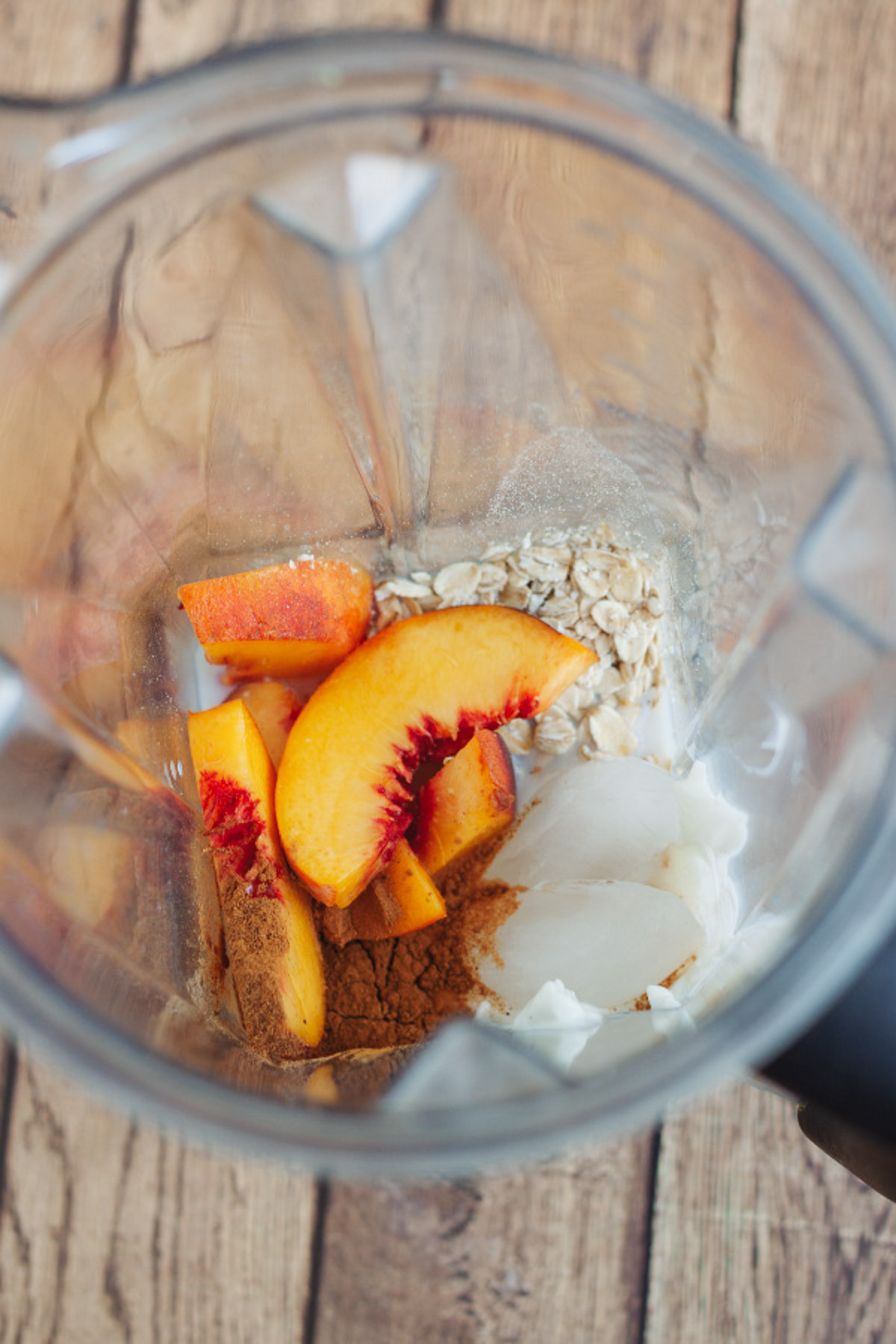 Top view into a blender jar with peaches and other ingredients to make a peach smoothie with yogurt.