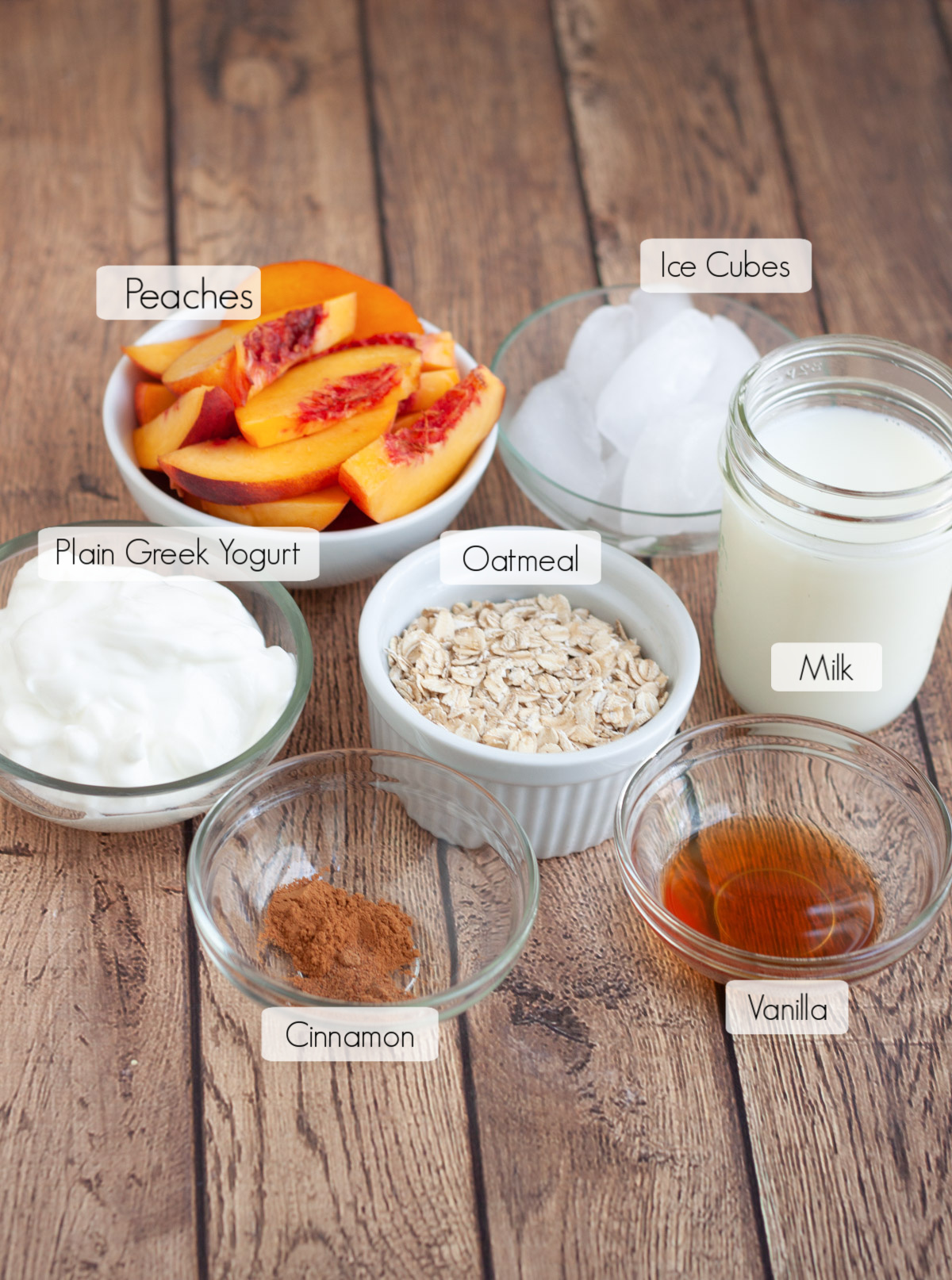 Ingredients in bowls with labels to make a peach pie smoothie with yogurt.