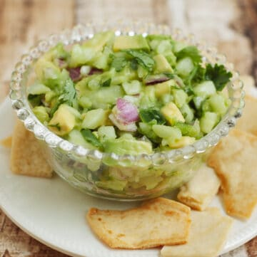 bowl of avocado cucumber salsa with pita chips on a white plate
