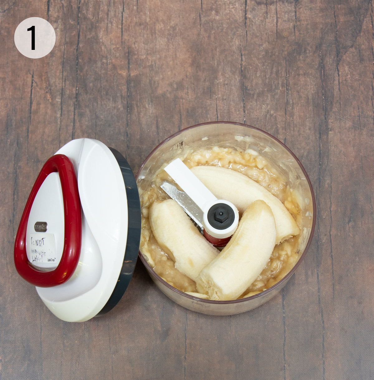 Handheld food chopper with bananas to puree and white lid with red handle on left side.