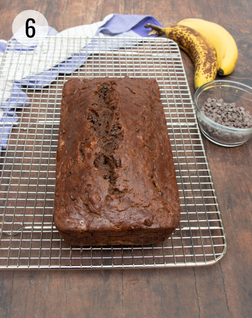 Chocolate Chip Banana Bread on a silver cooling rack with bananas, bowl of chocolate chips and blue and white towel in background.