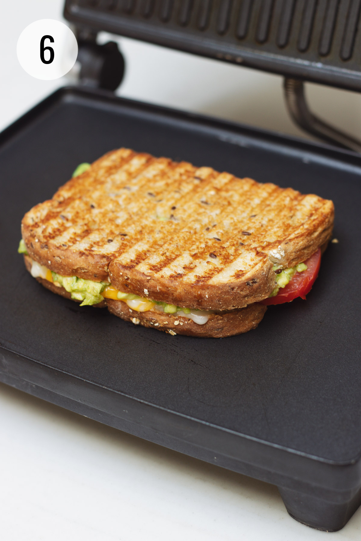 Grilled tomato and avocado grilled cheese sandwich on a panini maker.