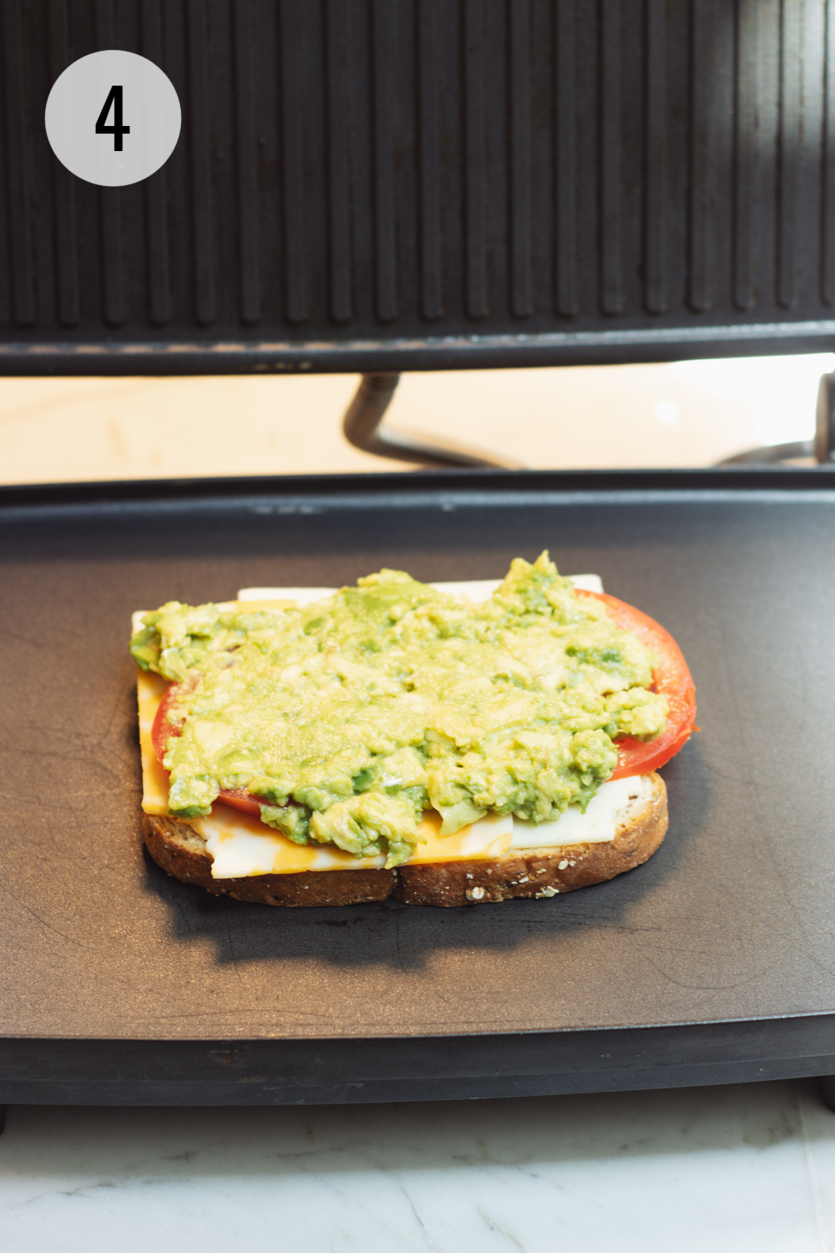 One slice of bread topped with cheese, tomato and avocado on a panini maker.