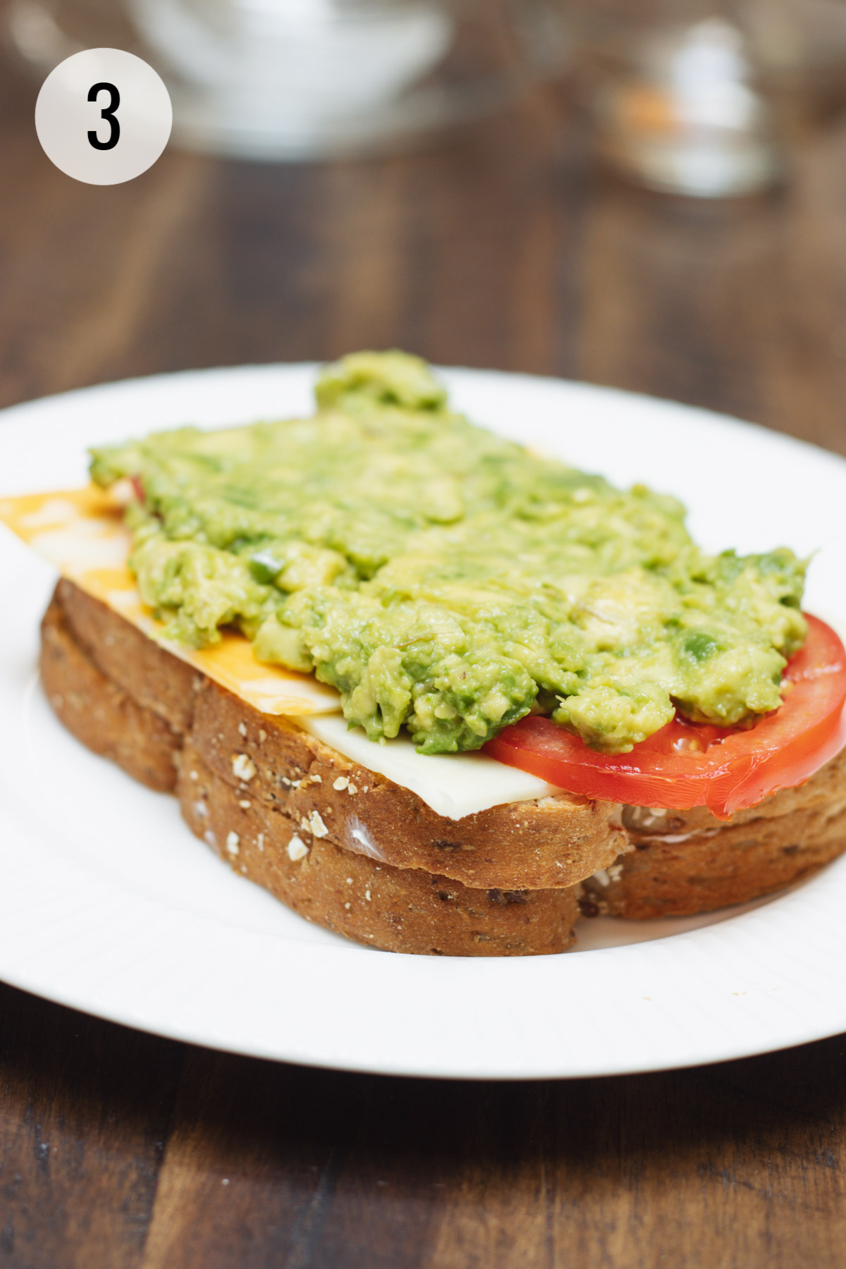 Two slices of bread topped with cheese, tomato and smashed avocado placed on a white plate.