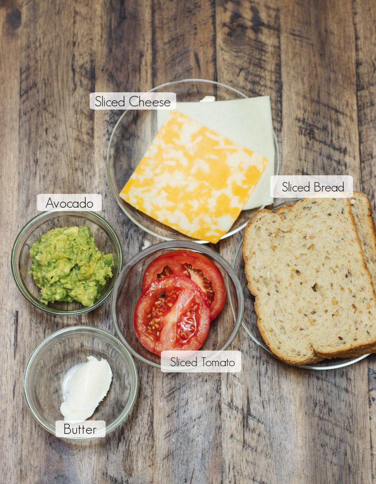 Labeled ingredients in bowls to make a tomato and avocado grilled cheese sandwich.