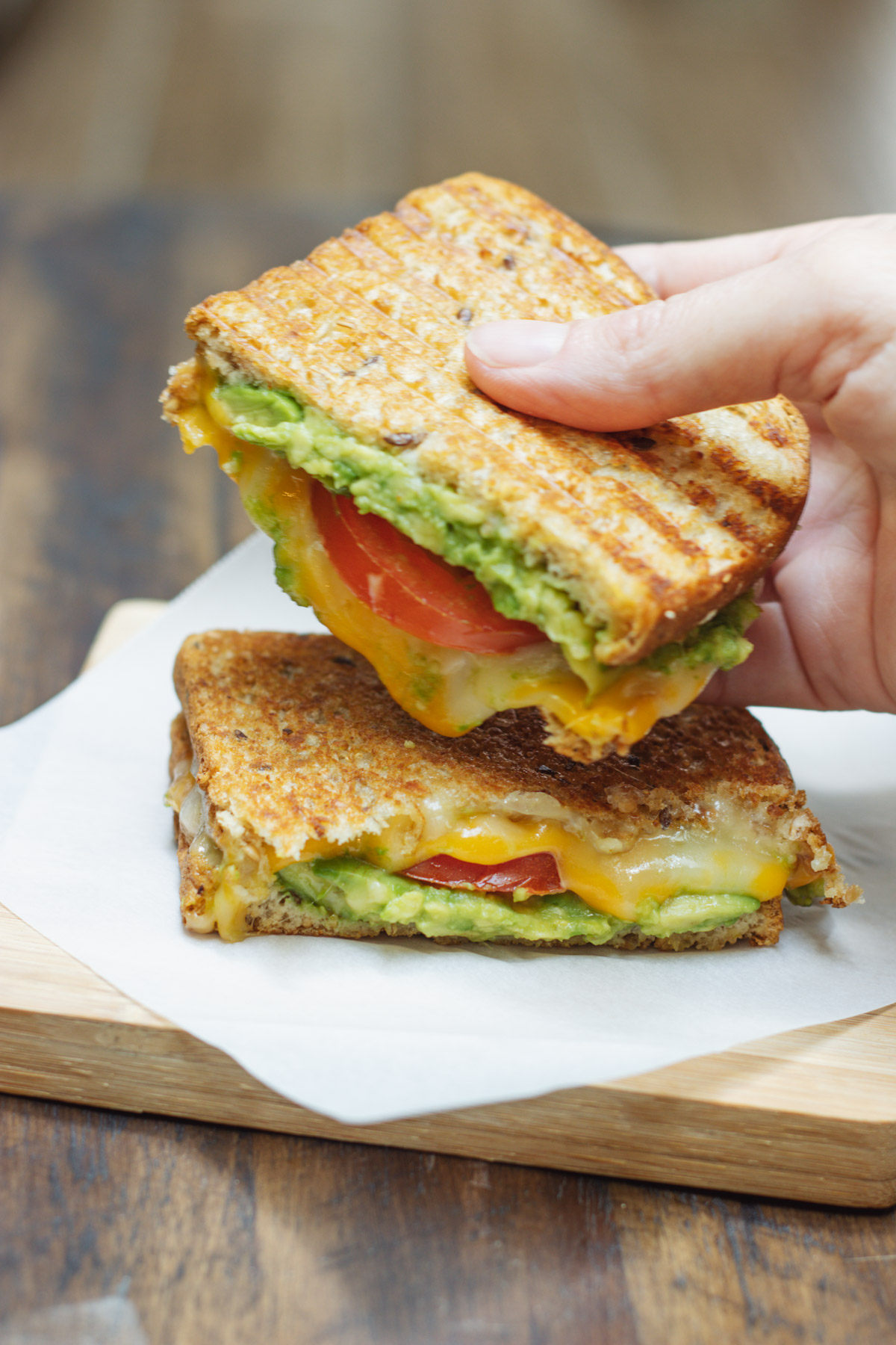 Two halves of a tomato and avocado grilled cheese sandwich on a wooden board with hand holding one half.